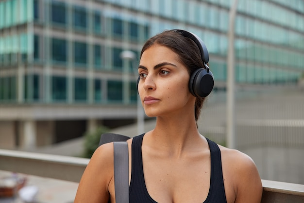 Horizontal shot of pensive brunette sportswoman going to have training listens music in wireless headphones while strolling in downtown looks away poses against blurred