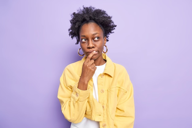 Horizontal shot of pensive dark skinned young woman makes choice keeps index finger on lips thinks deeply about something