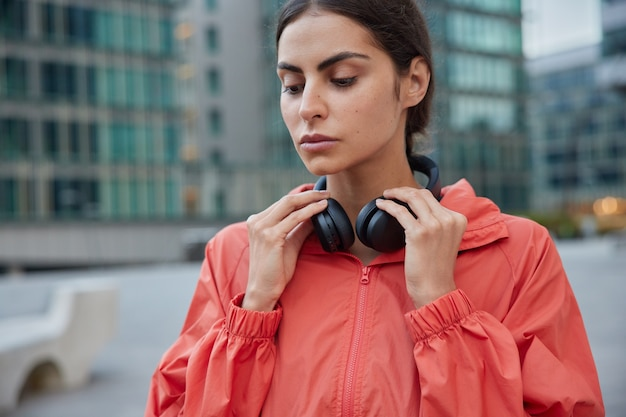 Horizontal shot of pensive motivated sportswoman focused down listens music in modern sound accessory with high volume spends free time for morning workout in urban city takes break from jogging