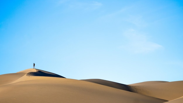 Horizontal shot of a person standing on sand dunes in a desert with the blue sky in the back