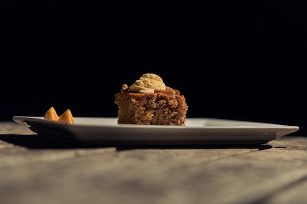 Inquadratura orizzontale di un pezzo di torta su un piatto bianco su una superficie di legno