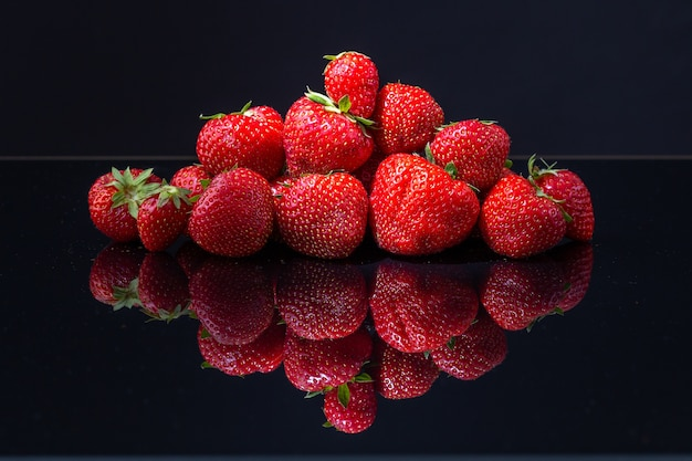 Horizontal shot of a pile of red croatian strawberries on a black reflecting surface