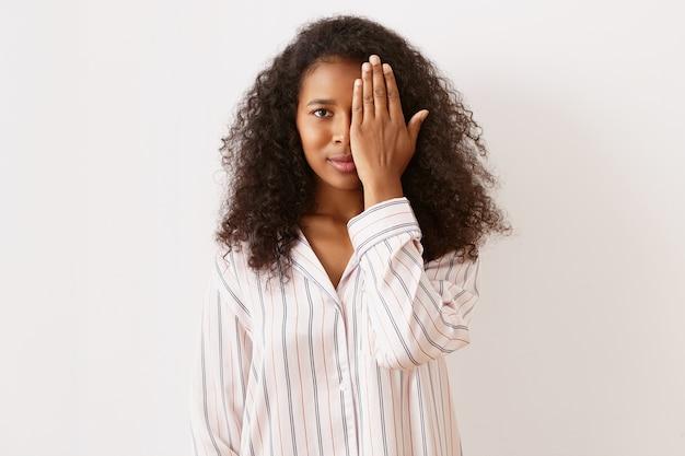 Inquadratura orizzontale di giocosa adorabile giovane donna afroamericana con voluminosi capelli neri e pelle abbronzata marrone in posa al muro bianco in pigiama di raso a righe, che copre un occhio con la mano