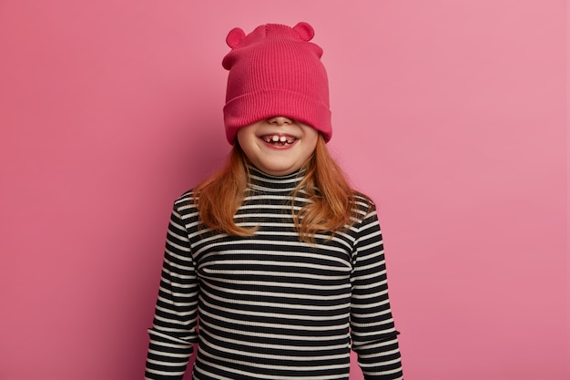 Horizontal shot of playful ginger little girl cloeses eyes with hat, wears striped jumper, has funny face, poses on pink pastel wall, hides under headgear, plays with friends or parents