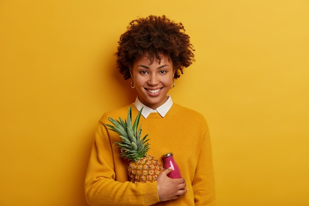 Colpo orizzontale della ragazza felice dall'aspetto piacevole con l'acconciatura afro, tiene ananas maturo e frullato, posa con frutta esotica, ha un ampio sorriso a trentadue denti, sguardo diretto, isolato sulla parete gialla