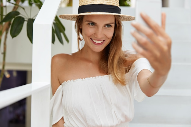 Horizontal shot of pleasant looking relaxed female poses of smart phone for making selfie portrait and shares photo with friends in social networks, boasts about her good summer rest