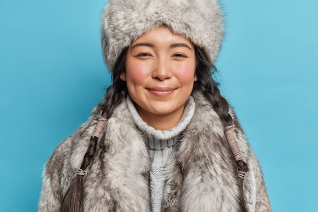 Horizontal shot of pleased brunette woman with two pigtails looks delighted at front wears fur hat and coat prepares for winter cold being inhabitant of northern pole isolated over blue studio wall