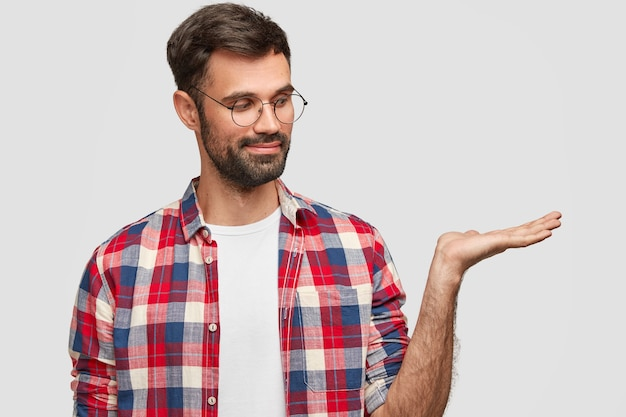 Horizontal shot of pleased man has thick bristle, raises palm, pretends holding something, wears checkered shirt with spectacles, stands against white wall