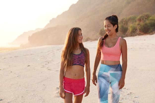 Inquadratura orizzontale di felice madre e figlia parlano durante la passeggiata all'aperto