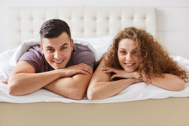 Horizontal shot of pleased satisfied family couple lie on comfortable bed, being in good mood after unforgettable night. lovely curly woman lies close to her boyfriend. relationship concept.