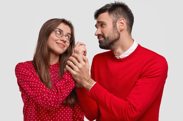 Horizontal shot of pleased woman looks at husband who has pleading expression and holds her hand, wear red clothes, have pleasant talk, isolated over white background. people