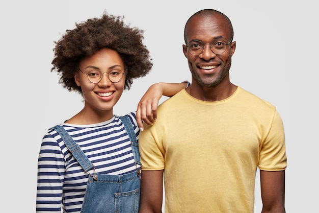 Horizontal shot of pleased young african american man and woman have gentle smiles