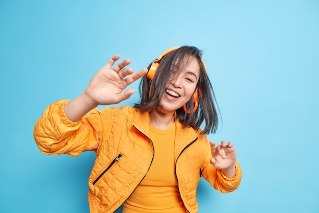 Horizontal shot of positive asian girl has natural brunette hair flying in air raises palms moves with rhythm of music enjoys good quality sound via wireless headphones wears jacket