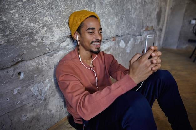 Colpo orizzontale di ragazzo dalla pelle scura barbuto positivo in maglione rosa, pantaloni blu, pantaloni e berretto senape che si siede sul pavimento di legno con lo smartphone in mano e ascolta la musica con gli auricolari