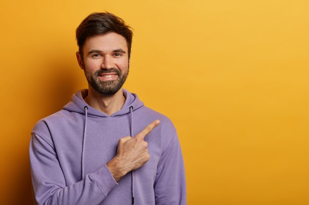 Horizontal shot of positive bearded man indicates at blank space, smiles joyfully, shows nice advertisement, wears violet sweatshirt, isolated over yellow wall. people and promo concept
