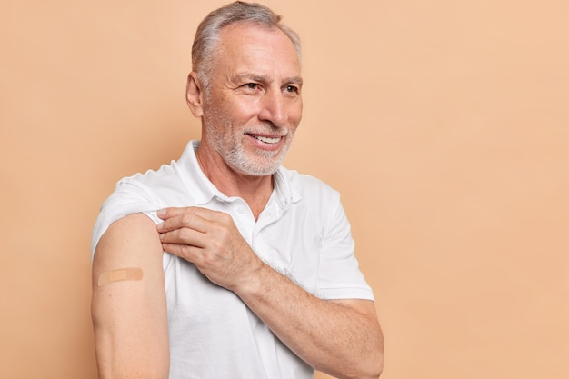 Horizontal shot of positive bearded old man shows arms with adhesive plaster get vaccinated against coronovirus happy to get second dose to reduce risk of getting seriously ill or dying from covid 19