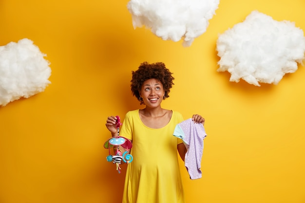 Horizontal shot of positive curly haired pregnant future woman awaits for baby birth, dressed in yellow dress, holds mobile and singlet, looks above on clouds. pregnancy and expectation concept