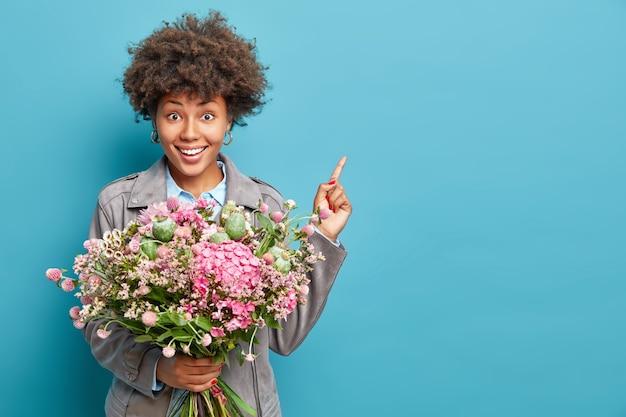 Il colpo orizzontale della donna dai capelli riccia positiva vestita in giacca grigia punta su uno spazio vuoto tiene il mazzo di fiori festeggia il compleanno isolato sopra la parete blu