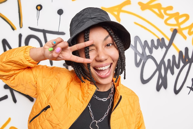 Horizontal shot of positive hipster girl males keace gesture over eye smiles broadly has fun in public place wears trendy hat yellow jacket poses against drawn graffiti wall