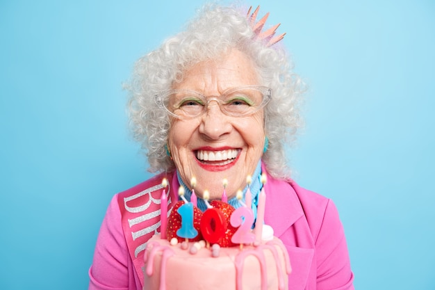 Horizontal shot of positive wrinkled european woman holds birthday cake dressed in stylish clothes for special occasion wears bright makeup looks beautiful and optimistic