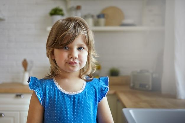Inquadratura orizzontale della bambina graziosa di 5 anni con i capelli biondi in posa nella cucina moderna, labbra imbronciate, con divertente espressione facciale. bambino femminile europeo che trascorre la giornata a casa dopo l'asilo