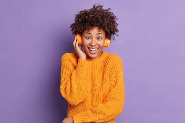 Inquadratura orizzontale della bella donna afro-americana con i capelli ricci risatine ascolta positivamente piacevole melodia indossa cuffie stereo indossa maglione arancione lavorato a maglia