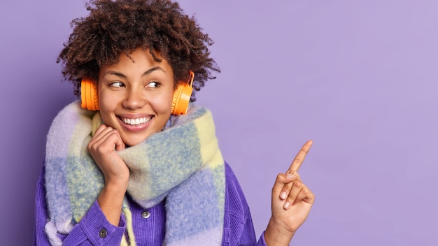 Horizontal shot of pretty afro american woman with broad smile white teeth presents something points at upper right corner listens music via headphones wears warm scarf around neck. look there