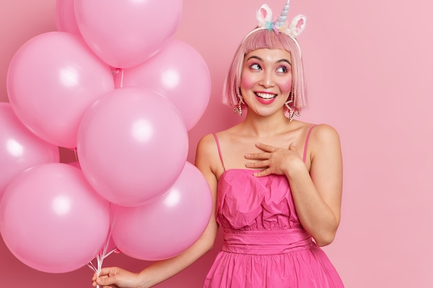 Horizontal shot of pretty cheerful birthday girl accepts congratulations smiles pleasantly holds helium balloons
