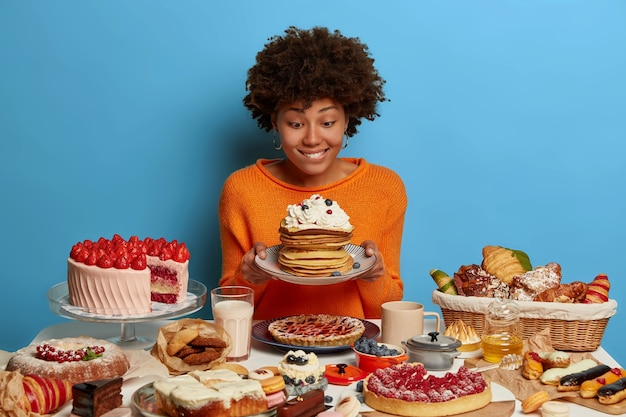 Horizontal shot of pretty curly haired woman holds plate with tasty pancakes, bites lips and feels temptation, has delicious food on table, isolated on blue wall.