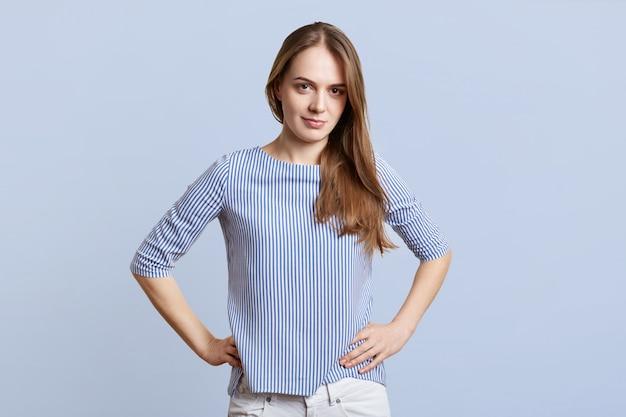 Horizontal shot of pretty female in stylish clothing keeps hands on waist