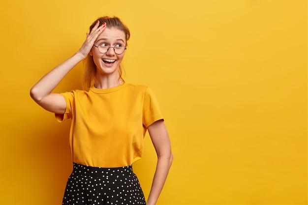 Horizontal shot of pretty joyful woman looks away keeps hand on head smiles broadly wears basic t shirt and skirt optical eyeglasses isolated over yellow wall blank space for your advert