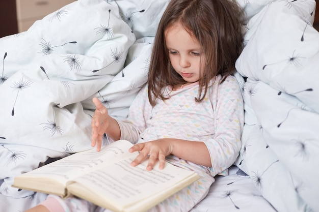 Horizontal shot of pretty little girl reading interesting book in her room while lying in bed under blanket with dandelion, looks concentrated and serious, cute dark haired female child rests at home.