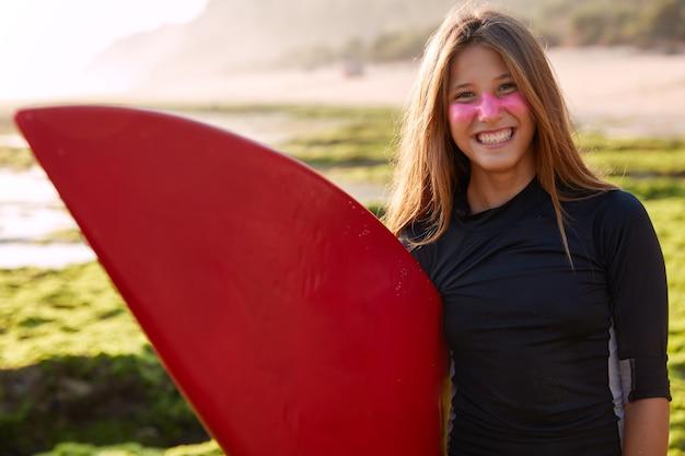 Colpo orizzontale di giovane donna caucasica piuttosto sorridente con capelli lisci lunghi