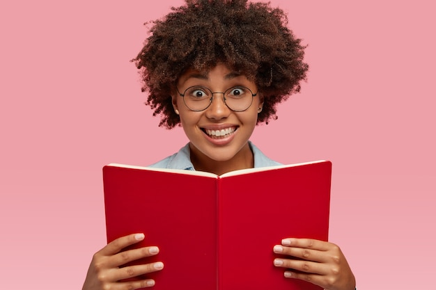 Horizontal shot of pretty smiling girl with pleasant facial expression, carries textbook, wears spectacles, prepares for examination, isolated over pink wall. people, ethnicity and literacy concept