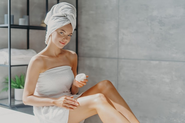 Horizontal shot of pretty woman applies cosmetic cream on skin, poses wrapped in towel, undergoes beauty procedures after taking shower, poses at home in bathroom.