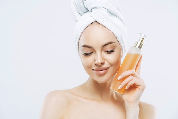 Horizontal shot of pretty woman with healthy skin, natural makeup, uses perfume spray, has pleased expression, natural beauty, looks down, wears bath towel on head, isolated over white wall