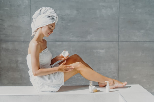 Horizontal shot of pretty woman with slender legs puts moisturising cream on healthy skin enjoys beauty routine after taking bath poses in bathroom wrapped in towel enjoys softness after lotion
