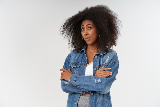 Horizontal shot of pretty young dark skinned female with curly hair keeping hands folded, looking aside dreamily and biting underlip, isolated over white wall