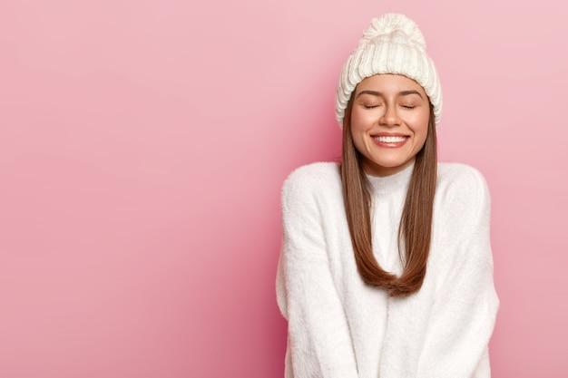 Inquadratura orizzontale di una donna abbastanza giovane con i capelli scuri, tiene gli occhi chiusi, sorride piacevolmente, mostra denti bianchi perfetti, gode di comfort in un maglione nuovo acquistato, cappello caldo