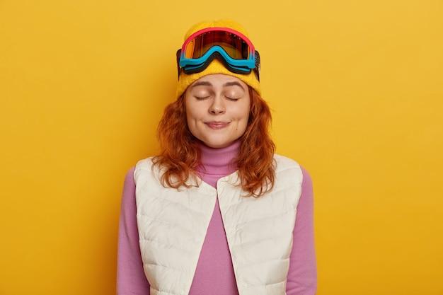 Inquadratura orizzontale della bella giovane donna sta con gli occhi chiusi, vestito con abiti caldi e comodi, indossa la maschera da snowboard per lo sci, isolato su sfondo giallo