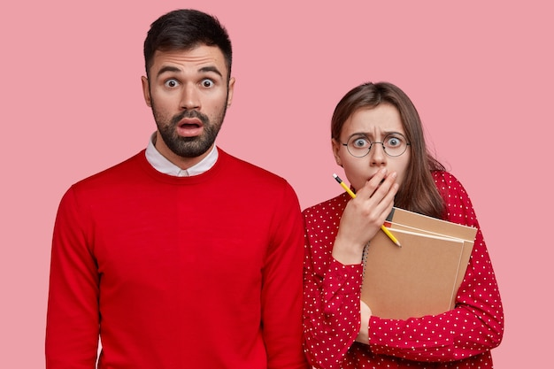 Horizontal shot of puzzled bearded man in red sweater, frightened girlfriend with pencil and spiral notepad