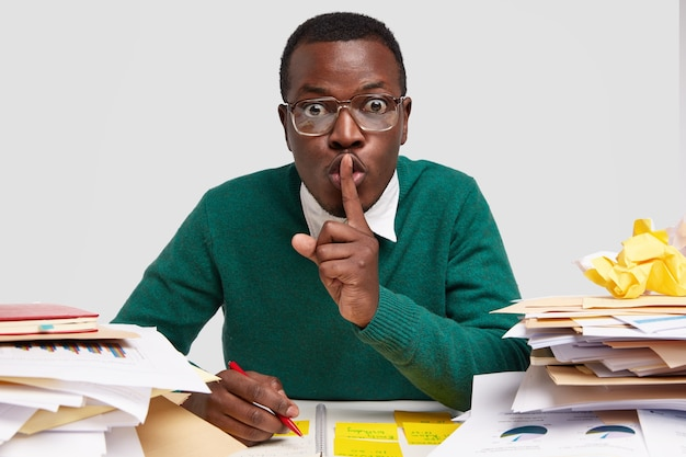 Inquadratura orizzontale di un architetto maschio perplesso fa un gesto di silenzio, medita su un nuovo progetto, fa contabilità, scrive, usa stick per annotare le informazioni