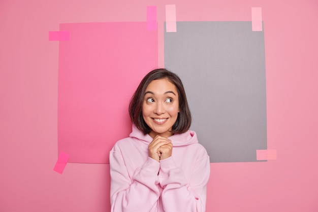 Horizontal shot of satisfied asian woman keeps hands together smiles pleasantly wears hoodie thinks about something pleasant poses against pink wall with two plastered sheets of paper
