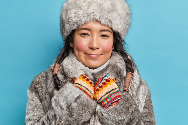 Horizontal shot of satisfied asian woman looks happily at front wears fur cap and coat enjoys fantastic winter time isolated over blue wall