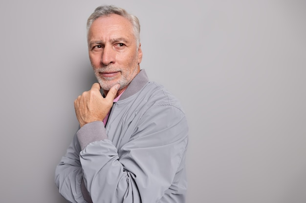 Horizontal shot of satisfied thoughtful wrinkled grandfather holds chin looks away