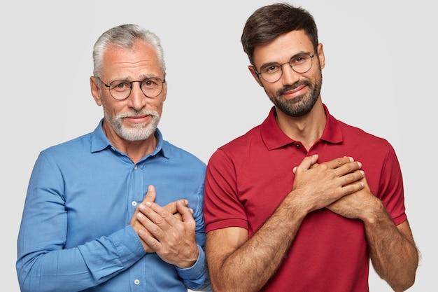 Inquadratura orizzontale di due uomini soddisfatti di età diversa, fanno un gesto di gratitudine, si sentono grati alle persone generose, hanno espressioni soddisfatte, isolato sopra il muro bianco. generazione, linguaggio del corpo
