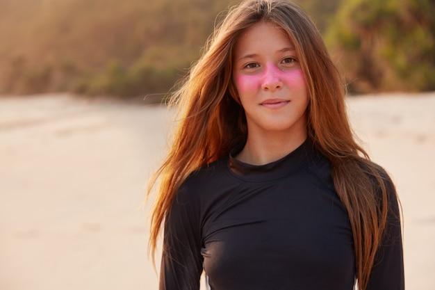 Inquadratura orizzontale di giovane donna soddisfatta con zinco da surf o pasta rosa, ha un aspetto affascinante, vestita in costume da bagno casual