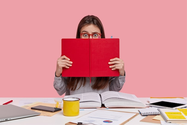 Horizontal shot of scared puzzled lady covers face with red textbook, uses modern technologies