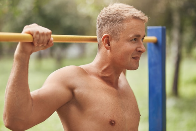 Horizontal shot of self assured young experienced strong sportsman has muscles