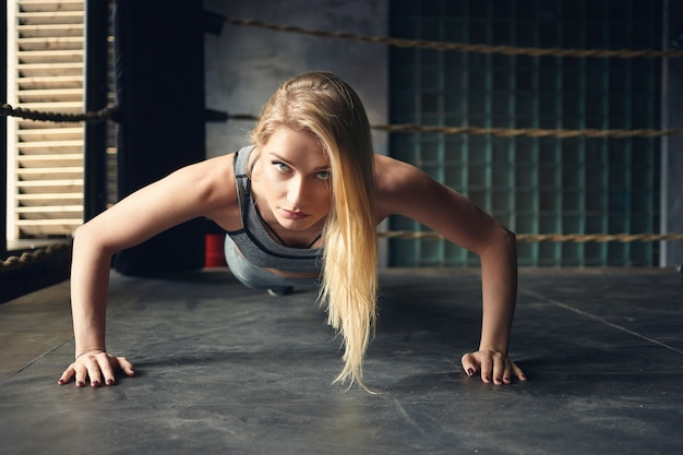 Horizontal shot of self determined gorgeous young sportswoman with loose dyed hair doing push ups planting hands widely on floor inside boxing ring